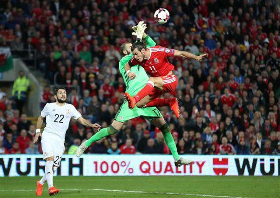 Wales' Gareth Bale, right, and Georgia goalkeeper Giorgi Loria battle for the ball during the 2018 World Cup qualifying, group D soccer match, Wales versus Georgia at the Cardiff City Stadium, Cardiff, Wales, Sunday Oct. 9, 2016. (Nick Potts/PA via AP)