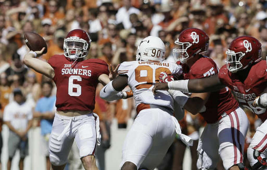 Oklahoma quarterback Baker Mayfield (6) throws a touchdown pass as offensive linemen Dru Samia (75) and Erick Wren (58) block Texas defensive end Charles Omenihu (90) during the second half of an NCAA college football game in Dallas, Saturday, Oct. 8, 2016. Oklahoma wide receiver Dede Westbrook caught the pass and Oklahoma won 45-40. (AP Photo/LM Otero)