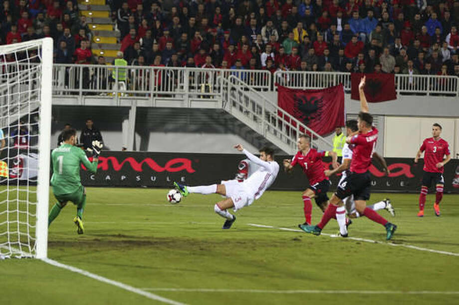 Spain's Gerard Pique, center, shoots on goal during their World Cup Group G qualifying soccer match at Loro Borici Stadium, in Shkoder, northern Albania, on Sunday, Oct. 9, 2016. (AP Photo/Visar Kryeziu)