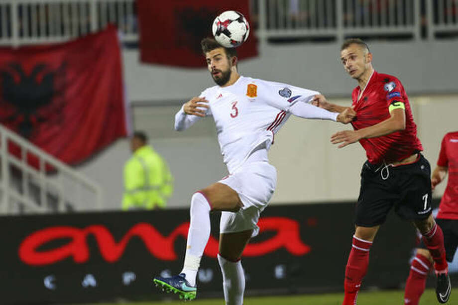 Albania's Ansi Agolli, right,fights for the ball with Spain's Gerard Pique during their World Cup Group G qualifying soccer match at Loro Borici Stadium, in Shkoder, northern Albania, on Sunday, Oct. 9, 2016. (AP Photo/Hektor Pustina)