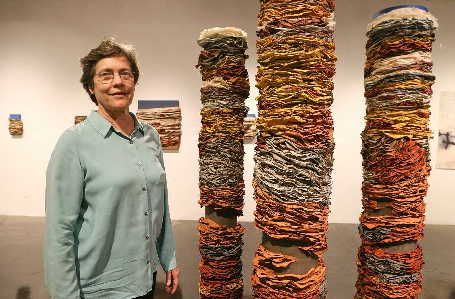 "Beck Whitehead beside ""Column I,"" ""Column II,"" and ""Column III"" in her exhibit titled ""Beck Whitehead & Pulparazzi,"" a survey of handmade paper and pulp painting, at the Southwest School of Art. Photo: Photos By Marvin Pfeiffer /San Antonio Express-News / Express-News 2016"