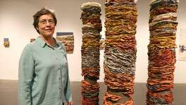 "Beck Whitehead beside ""Column I,"" ""Column II,"" and ""Column III"" in her exhibit titled ""Beck Whitehead & Pulparazzi,"" a survey of handmade paper and pulp painting, at the Southwest School of Art."