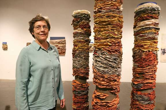 """Beck Whitehead beside """"Column I,"""" """"Column II,"""" and """"Column III"""" in her exhibit titled """"Beck Whitehead & Pulparazzi,"""" a survey of handmade paper and pulp painting, at the Southwest School of Art."""