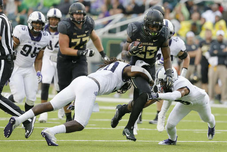 TCU safety Denzel Johnson (30) and safety Nick Orr, right, combine to stop Baylor running back Terence Williams (22) after a short run in the first half of an NCAA college football game, Saturday, Nov. 5, 2016, in Waco, Texas. (AP Photo/Tony Gutierrez)