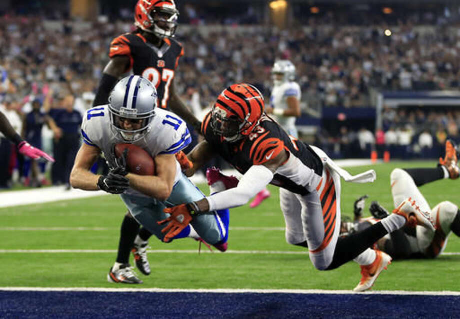 Dallas Cowboys wide receiver Cole Beasley (11) leaps into the end zone for a touchdown after catching a pass as Cincinnati Bengals free safety George Iloka (43) defends in the first half of an NFL football game, Sunday, Oct. 9, 2016, in Arlington, Texas. (AP Photo/Ron Jenkins)