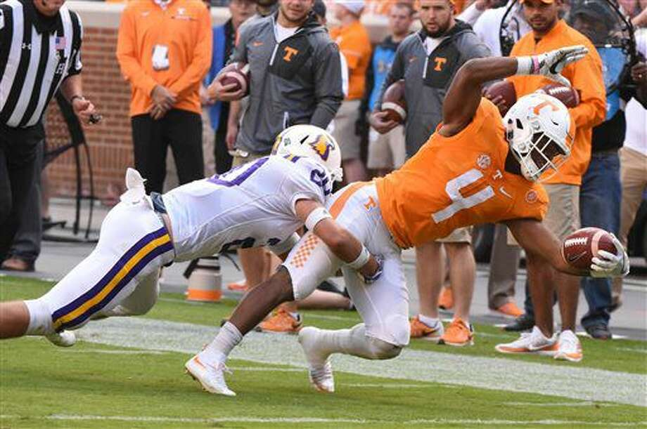 Tennessee running back John Kelly (4) is pulled to a stop by Tennessee Tech safety Clay Davis (20) during the first half of an NCAA college football game Saturday, Nov. 5, 2016, in Knoxville, Tenn. (Michael Patrick/Knoxville News Sentinel via AP)