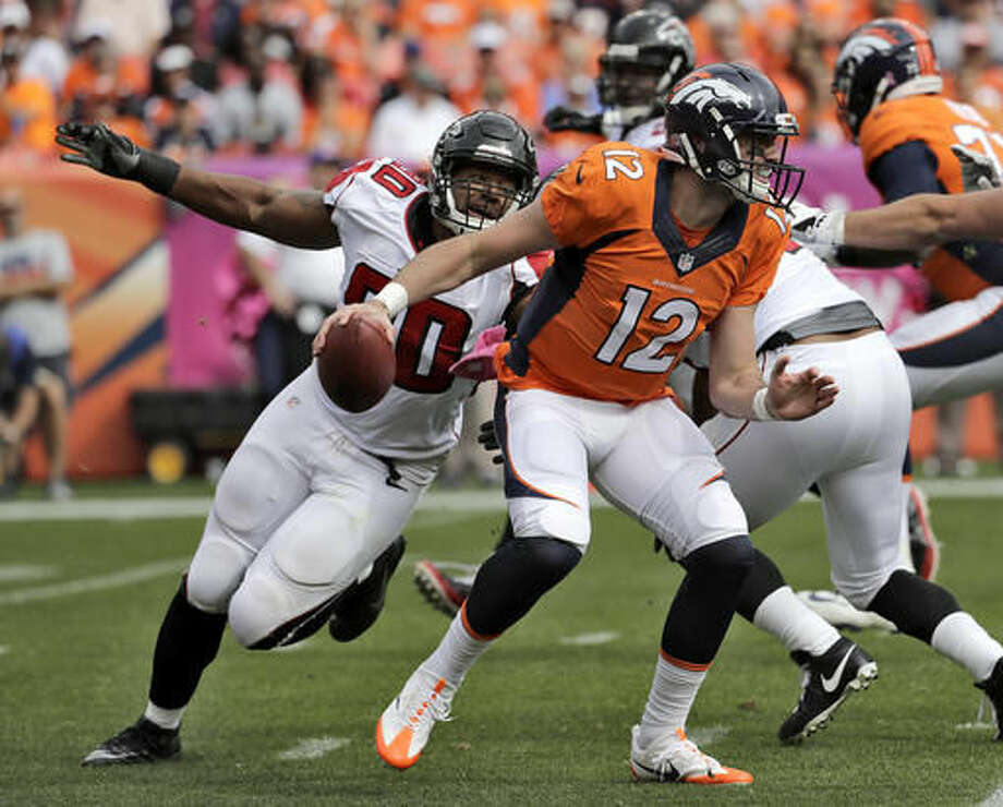 Denver Broncos quarterback Paxton Lynch (12) scrambles as Atlanta Falcons defensive end Derrick Shelby (90) pursues during the first half of an NFL football game, Sunday, Oct. 9, 2016, in Denver. (AP Photo/Jack Dempsey)