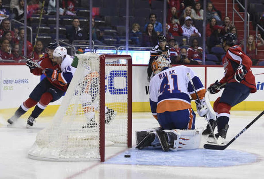 New York Islanders goalie Jaroslav Halak (41) looks back after Washington Capitals left wing Andre Burakovsky (65), of Austria, left, scored pressured by New York Islanders defenseman Thomas Hickey (14) during first period of an NHL preseason hockey game, Sunday, Oct. 9, 2016, in Washington. (AP Photo/Molly Riley)