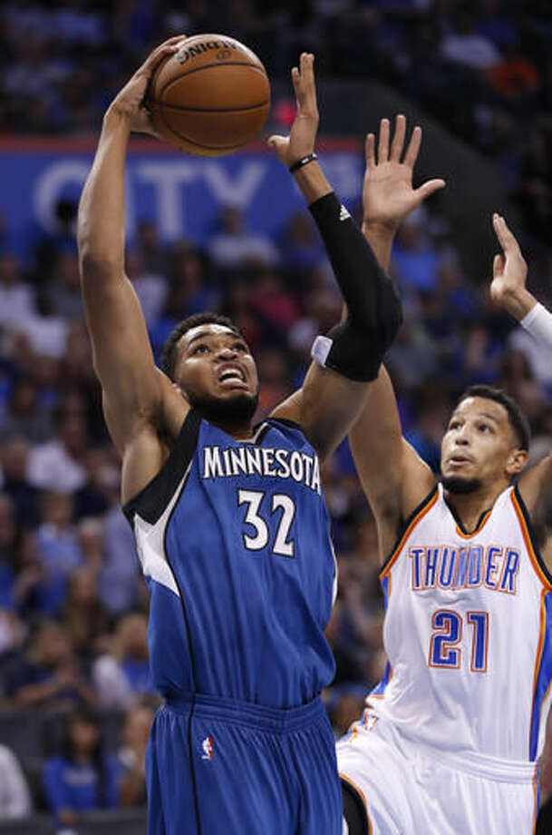 Minnesota Timberwolves center Karl-Anthony Towns (32) goes to the basket ahead of Oklahoma City Thunder guard Andre Roberson (21) during the first half of an NBA basketball game in Oklahoma City, Saturday, Nov. 5, 2016. (AP Photo/Alonzo Adams)
