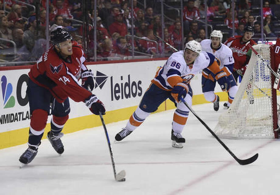 Washington Capitals defenseman John Carlson (74) passes the puck in front of New York Islanders left wing Nikolay Kulemin (86), of Russia, during second period of an NHL preseason hockey game, Sunday, Oct. 9, 2016, in Washington. (AP Photo/Molly Riley)