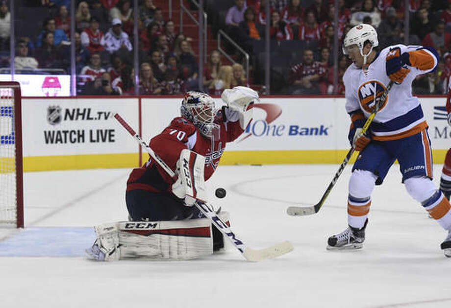 Washington Capitals goalie Braden Holtby (70) makes a save off a shot by New York Islanders right wing P.A. Parenteau (17), during second period of an NHL preseason hockey game, Sunday, Oct. 9, 2016, in Washington. (AP Photo/Molly Riley)
