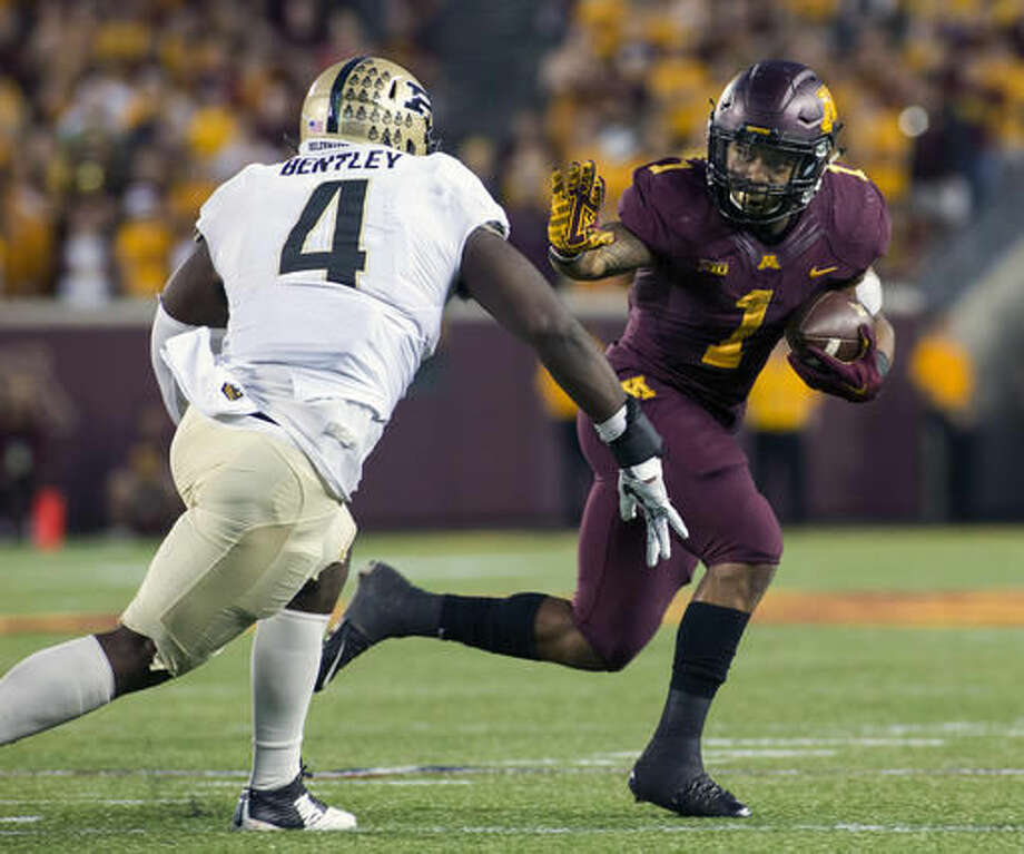 Minnesota running back Rodney Smith (1) looks to stiff-arm Purdue linebacker Ja'Whaun Bentley (4) on his way to a 14-yard touchdown run during the second half of an NCAA college football game, Saturday, Nov. 5, 2016, in Minneapolis. (AP Photo/Paul Battaglia)