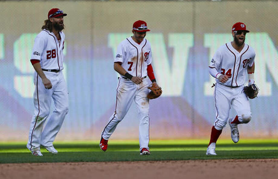 Washington Nationals' Jayson Werth (28), Trea Turner (7) and Bryce Harper (34) celebrate on the field following the last out of Game 2 of baseball's National League Division Series against the Los Angeles Dodgers at Nationals Park, Sunday, Oct. 9, 2016, in Washington. (AP Photo/Pablo Martinez Monsivais)