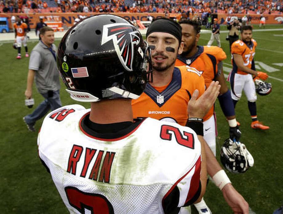 Atlanta Falcons quarterback Matt Ryan (2) greets Denver Broncos quarterback Paxton Lynch (12) after an NFL football game, Sunday, Oct. 9, 2016, in Denver. The Falcons won 23-16. (AP Photo/Jack Dempsey)