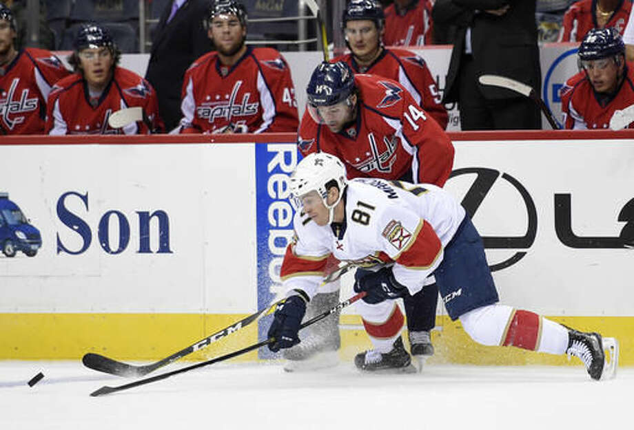 Florida Panthers center Jonathan Marchessault (81) fights for the puck against Washington Capitals right wing Justin Williams (14) during the first period of an NHL hockey game, Saturday, Nov. 5, 2016, in Washington. (AP Photo/Nick Wass)