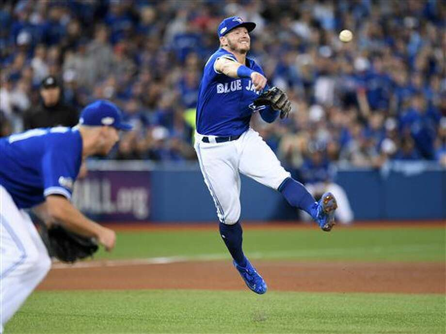 Toronto Blue Jays' Josh Donaldson (20) throws out Texas Rangers' Carlos Gomez (14) as pitcher Joe Biagini looks on during seventh inning game three American League Division Series action, in Toronto on Sunday, Oct. 9, 2016. (Frank Gunn/The Canadian Press via AP)