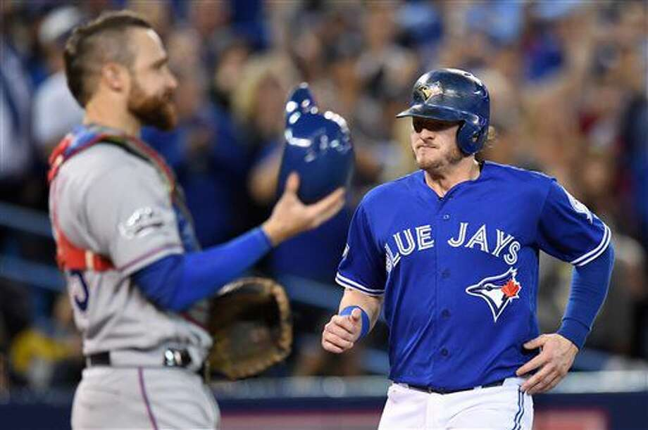 Toronto Blue Jays' Josh Donaldson, right, comes to score past Texas Rangers' catcher Jonathan Lucroy during third inning game three American League Division Series baseball action in Toronto on Sunday, Oct. 9, 2016. (Frank Gunn/The Canadian Press via AP)