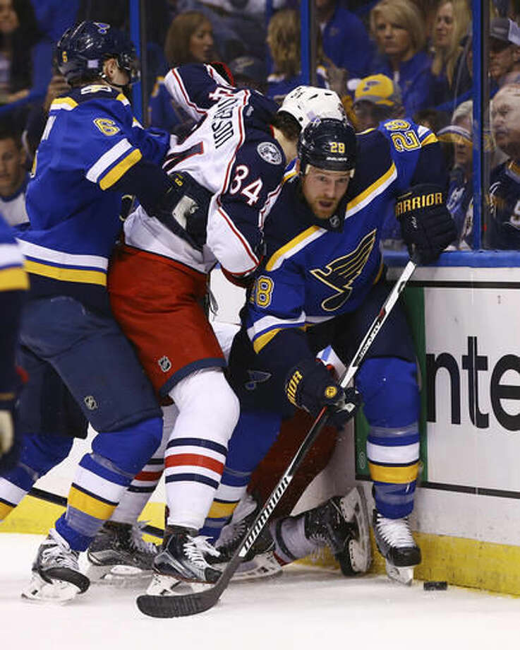 St. Louis Blues' Kyle Brodziak, right, pulls the puck out of a scrum as he is pressured by Columbus Blue Jackets' Josh Anderson during the first period of an NHL hockey game Saturday, Nov. 5, 2016, in St. Louis. (AP Photo/Billy Hurst)