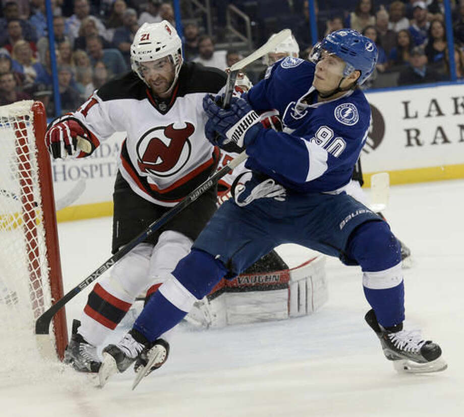 New Jersey Devils right wing Kyle Palmieri (21) and Tampa Bay Lightning center Vladislav Namestnikov (90) fight for position during the second period of an NHL hockey game Saturday, Nov. 5, 2016, in Tampa, Fla. (AP Photo/Jason Behnken)
