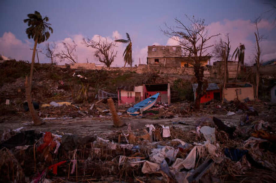A boat lies washed up amidst Haitian army buildings damaged by Hurricane Matthew, in a seaside fishing neighborhood in Port Salut, Haiti, Sunday, Oct. 9, 2016. Five days after the storm smashed into southwestern Haiti, some communities along the southern coast have yet to receive any assistance, leaving residents who have lost their homes and virtually all of their belongings struggling to find shelter and potable water.(AP Photo/Rebecca Blackwell)