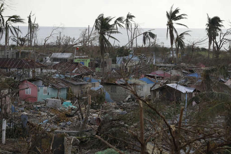 Debris lies scattered around buildings severely damaged by Hurricane Matthew, in a seaside fishing neighborhood of Port Salut, Haiti, Sunday, Oct. 9, 2016. Nearly a week after the storm smashed into southwestern Haiti, some communities along the southern coast have yet to receive any assistance, leaving residents who have lost their homes and virtually all of their belongings struggling to find shelter and potable water.(AP Photo/Rebecca Blackwell)