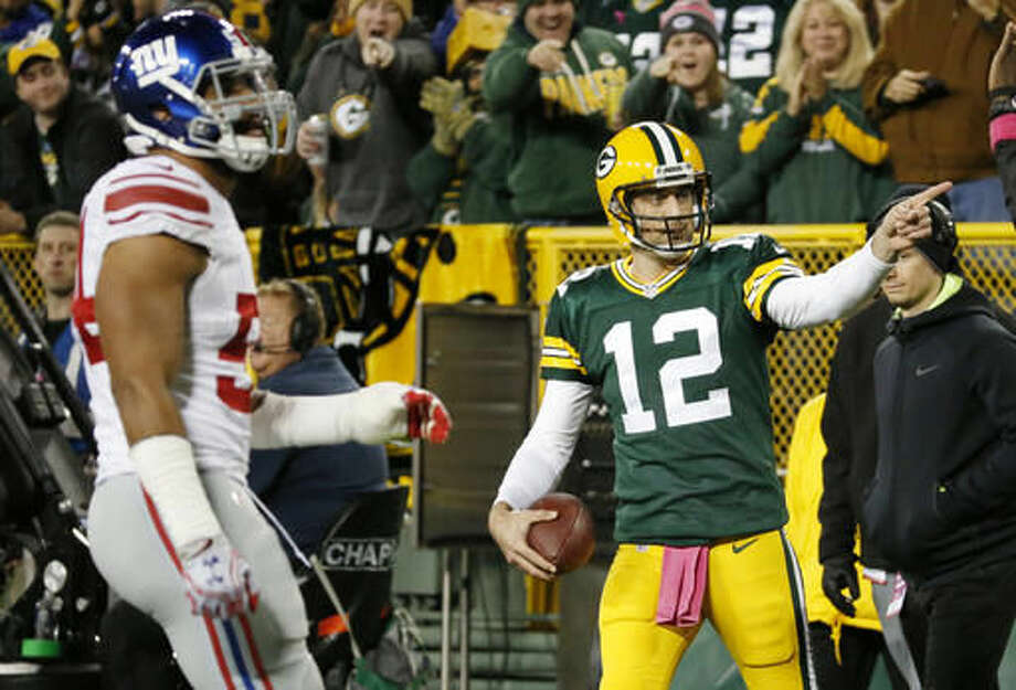 Green Bay Packers' Aaron Rodgers reacts to his first down run during the first half of an NFL football game against the New York Giants Sunday, Oct. 9, 2016, in Green Bay, Wis. (AP Photo/Mike Roemer)