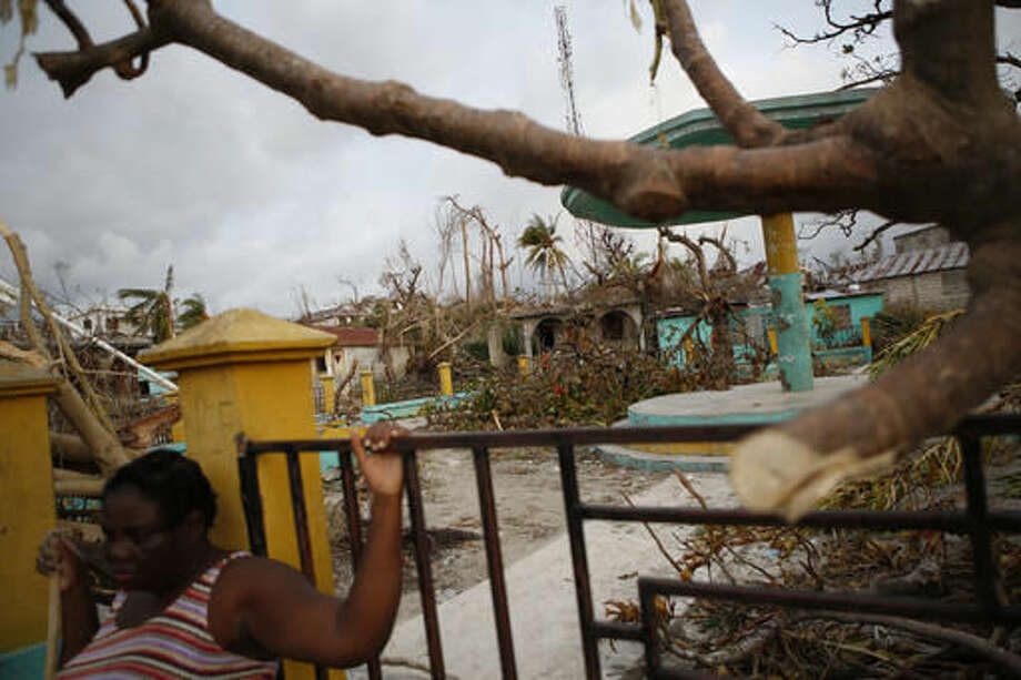 A woman pauses to rest against a fence as she cleans up debris in a seaside fishing neighborhood severely damaged by Hurricane Matthew, in Port Salut, Haiti, Sunday, Oct. 9, 2016. Nearly a week after the storm smashed into southwestern Haiti, some communities along the southern coast have yet to receive any assistance, leaving residents who have lost their homes and virtually all of their belongings struggling to find shelter and potable water.(AP Photo/Rebecca Blackwell)