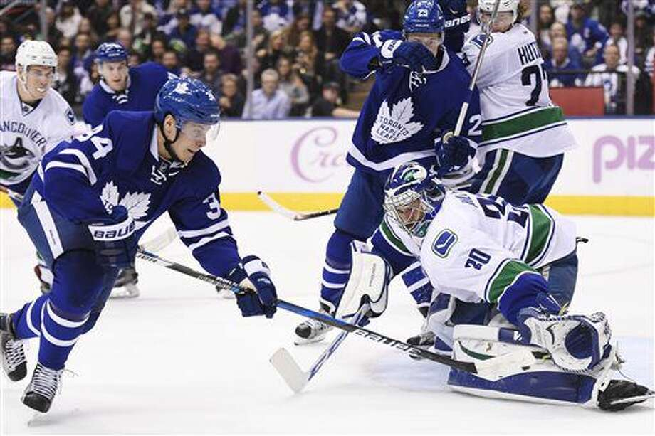 Vancouver Canucks goalie Ryan Miller (30) makes a save on Toronto Maple Leafs center Auston Matthews (34) during the second period of an NHL hockey game Saturday, Nov. 5, 2016, in Toronto. (Frank Gunn/The Canadian Press via AP)