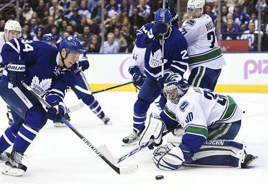 Vancouver Canucks goalie Ryan Miller (30) makes a save on Toronto Maple Leafs centre Auston Matthews (34) during the second period of an NHL hockey game Saturday, Nov. 5, 2016, in Toronto. (Frank Gunn/The Canadian Press via AP)