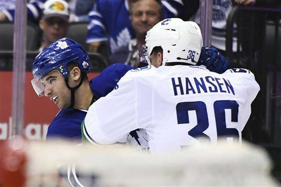 Toronto Maple Leafs center Nazem Kadri (43) and Vancouver Canucks right wing Jannik Hansen (36) fight during the third period of an NHL hockey game Saturday, Nov. 5, 2016, in Toronto. (Frank Gunn/The Canadian Press via AP)