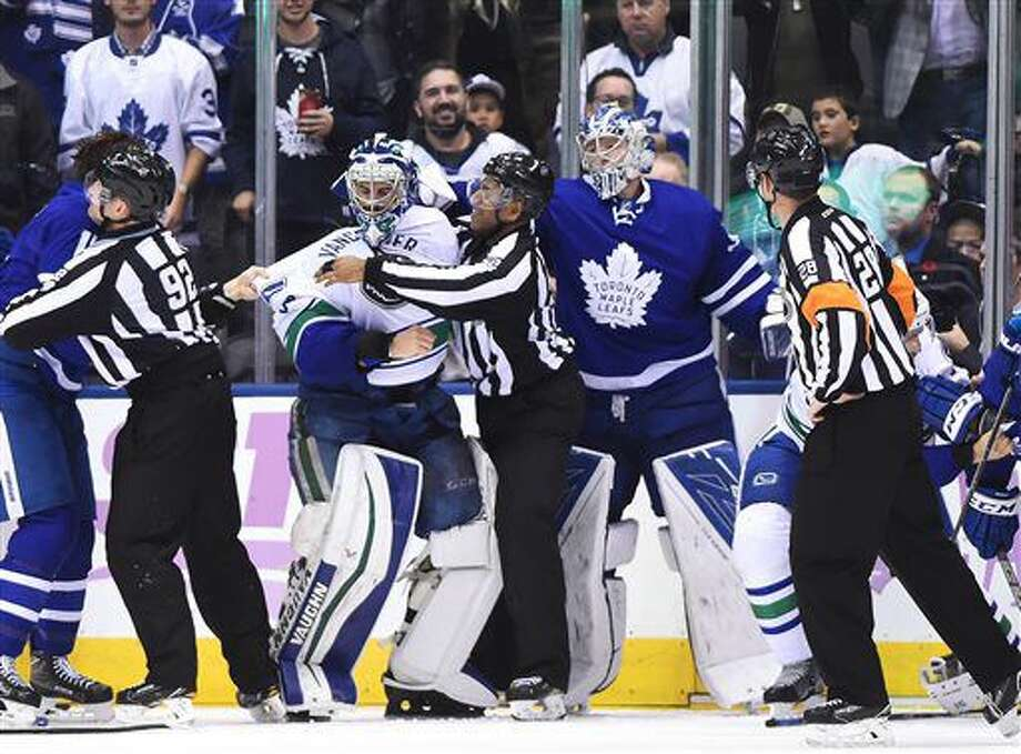 Vancouver Canucks goalie Ryan Miller (30) and Toronto Maple Leafs goalie Frederik Andersen (31) take part in a brawl during the third period of an NHL hockey game Saturday, Nov. 5, 2016, in Toronto. (Frank Gunn/The Canadian Press via AP)