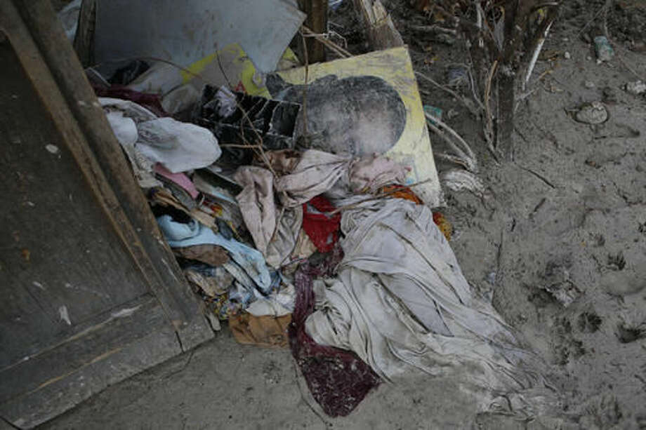 A water-damaged campaign poster lies amidst clothes and other household goods outside a home destroyed by Hurricane Matthew in a seaside fishing neighborhood of Port Salut, Haiti, Sunday, Oct. 9, 2016. Oct. 9 was the date set for Haiti's presidential elections, but they were postponed indefinitely after Hurricane Matthew struck nearly a week ago, killing hundreds and leaving whole communities without shelter or potable water. (AP Photo/Rebecca Blackwell)