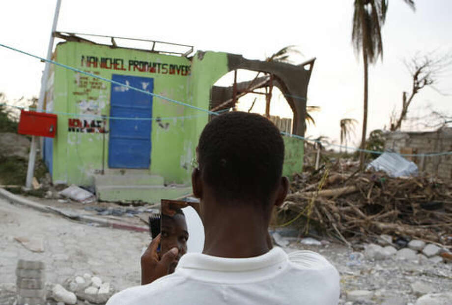 A young man uses a mirror to fix his hair in a seaside fishing neighborhood heavily damaged by Hurricane Matthew, in Port Salut, Haiti, Sunday, Oct. 9, 2016. Nearly a week after the storm smashed into southwestern Haiti, some communities along the southern coast have yet to receive any assistance, leaving residents who have lost their homes and virtually all of their belongings struggling to find shelter and potable water.(AP Photo/Rebecca Blackwell)