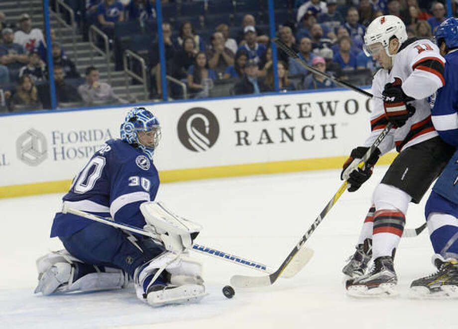 Tampa Bay Lightning goalie Ben Bishop (30) stops a shot from New Jersey Devils right wing PA Parenteau (11) during the third period of an NHL hockey game Saturday, Nov. 5, 2016, in Tampa, Fla. (AP Photo/Jason Behnken)