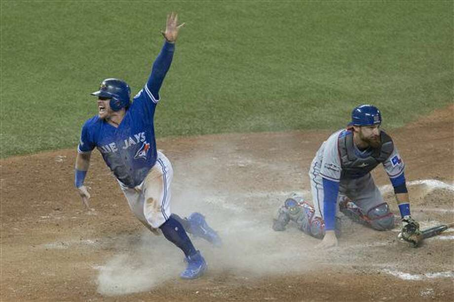 Toronto Blue Jays' Josh Donaldson, left, celebrates after scoring on a throwing error from Texas Rangers second baseman Rougned Odor as Texas Rangers catcher Jonathan Lucroy kneels on the plate during tenth inning American League Division Series action, in Toronto on Sunday, Oct. 9, 2016. (Chris Young/The Canadian Press via AP)