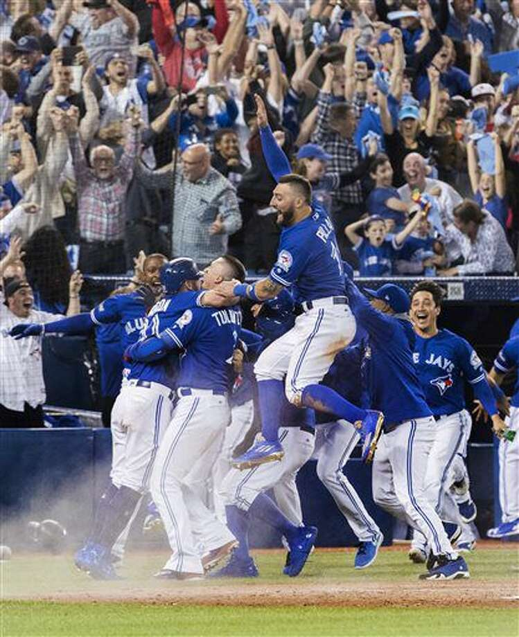 Toronto Blue Jays celebrate their walk-off win to eliminate the Texas Rangers during the tenth inning to win the American League Division Series in Toronto on Sunday, Oct. 9, 2016. (Mark Blinch/The Canadian Press via AP)
