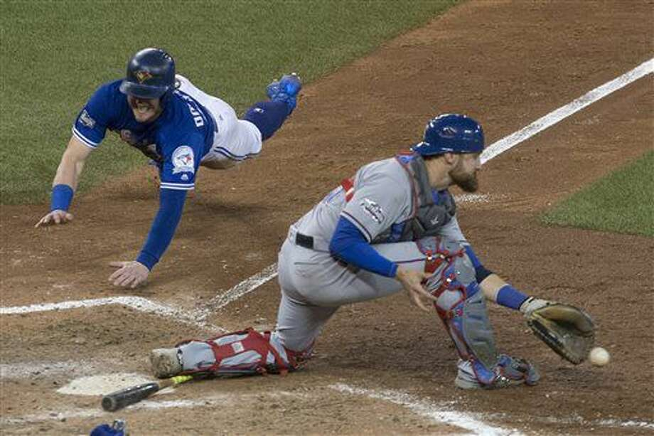 Toronto Blue Jays' Josh Donaldson, left, scores on a throwing error from Texas Rangers second baseman Rougned Odor as Texas Rangers catcher Jonathan Lucroy gathers up the ball during tenth inning American League Division Series action, in Toronto on Sunday, Oct. 9, 2016. (Chris Young/The Canadian Press via AP)