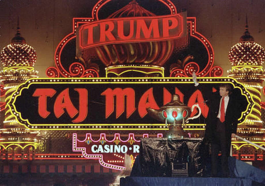 "FILE - In this April 5, 1990 file photo, Donald Trump stands next to a genie's lamp as the lights of his Trump Taj Mahal Casino Resort light up during ceremonies to mark its opening in Atlantic City, N.J. Trump opened his Trump Taj Mahal casino 26 years ago, calling it ""the eighth wonder of the world."" But his friend and fellow billionaire Carl Icahn is closing it Monday morning, making it the fifth casualty of Atlantic City's casino crisis. (AP Photo/Mike Derer, File)"