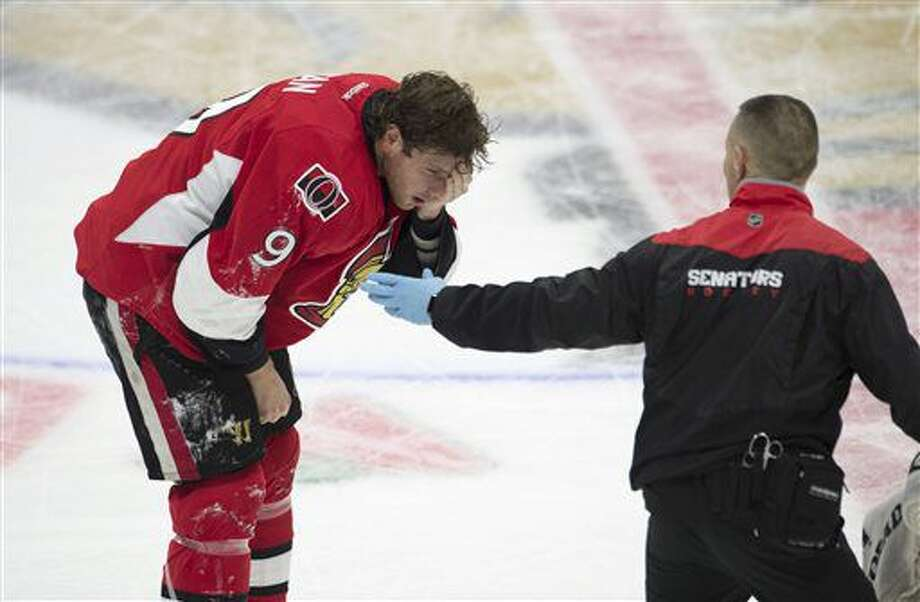 The Ottawa Senators trainer, right, helps right wing Bobby Ryan skate off the ice after being hit with a high stick by Buffalo Sabres defenseman Dmitry Kulikov during third-period NHL hockey game action Saturday, Nov. 5, 2016, in Ottawa, Ontario. (Adrian Wyld/The Canadian Press via AP)