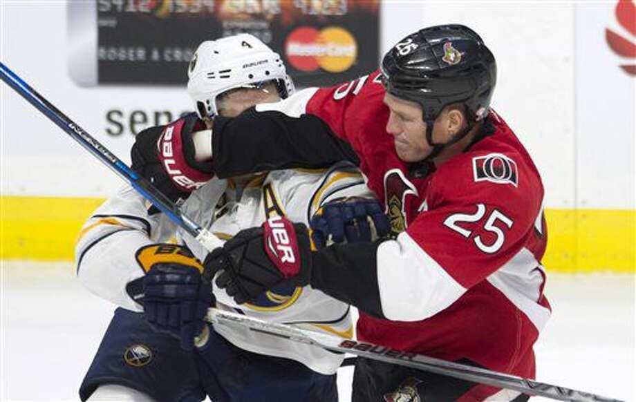 Ottawa Senators right wing Chris Neil (25) ties up Buffalo Sabres defenseman Josh Gorges during third-period NHL hockey game action Saturday, Nov. 5, 2016, in Ottawa, Ontario. (Adrian Wyld/The Canadian Press via AP)