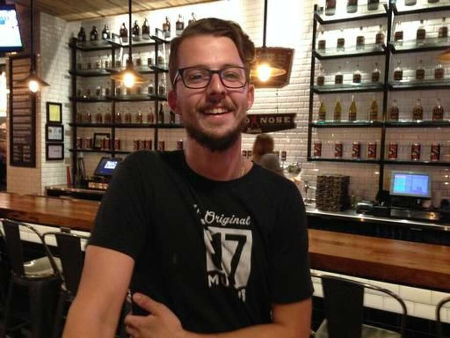 Andy Fox, 24, of Lansing, Mich., poses for a photo after watching parts of the second presidential debate while working as a server on Sunday, Oct. 9, 2016, at the Lansing Brewing Co. in Lansing. Fox said he is unlikely to vote for Hillary Clinton or Donald Trump. (AP Photo/David Eggert)