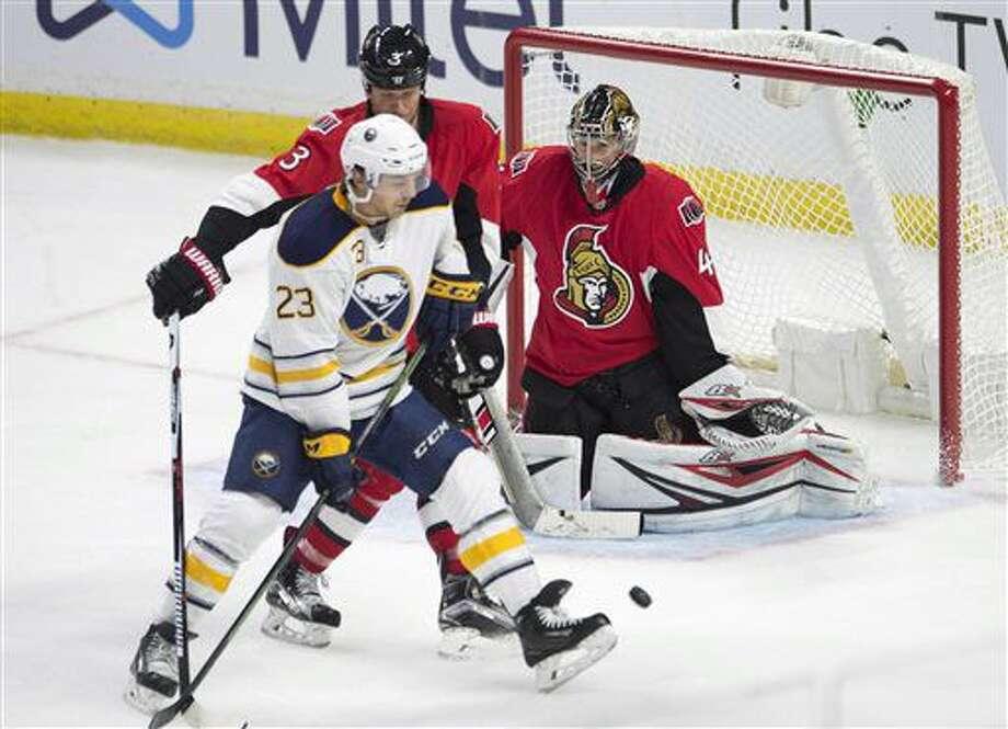 Buffalo Sabres center Sam Reinhart (23) tries to screen Ottawa Senators goalie Craig Anderson, right, under pressure from Senators defenseman Marc Methot during third-period NHL hockey game action Saturday, Nov. 5, 2016, in Ottawa, Ontario. (Adrian Wyld/The Canadian Press via AP)