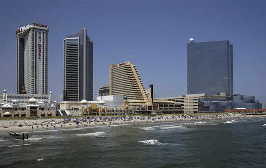 """FILE - In this July 23, 2014 file photograph, the Revel Casino Hotel, right, stands along the Boardwalk near Trump Taj Mahal Casino, left, with its Chairman Tower, and the Showboat Casino Hotel, second right, in Atlantic City, N.J. Trump opened his Trump Taj Mahal casino 26 years ago, calling it """"the eighth wonder of the world."""" But his friend and fellow billionaire Carl Icahn is closing it Monday morning, making it the fifth casualty of Atlantic City's casino crisis. (AP Photo/Mel Evans, File)"""