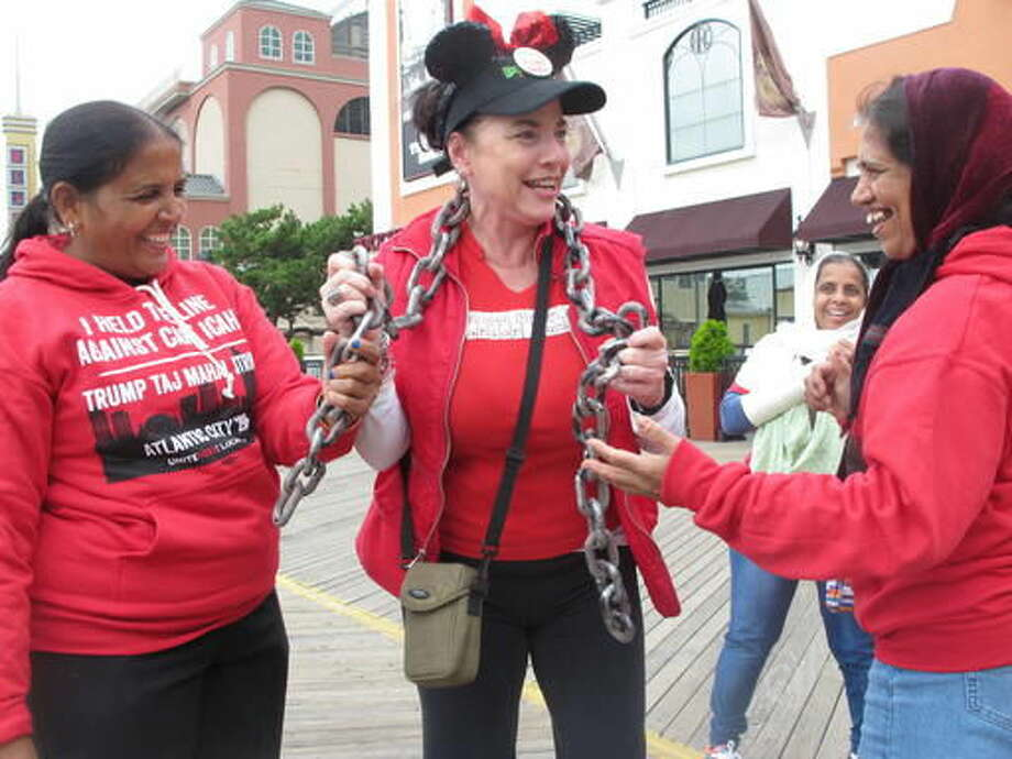 In this Oct. 5, 2016 photo, Tina Condos, center, greets fellow strikers outside the Trump Taj Mahal casino in Atlantic City N.J., while wearing chains to symbolize what she said were oppressive working conditions at the casino, where she had worked since the day it opened in 1990. The casino is to close at 6 a.m. on Monday Oct. 10, 2016, the fifth Atlantic City casino to go out of business since 2014. (AP Photo/Wayne Parry)
