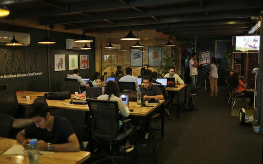 In this Aug. 19, 2016 photo, young Indian entrepreneurs and freelancers work at Innov8, a lax co-working space in New Delhi, India. As India emerges as one of the biggest markets in the world for tech-based startups, workspaces are transforming from traditional and hierarchal, to relaxed and bar-like. With more than 4,200 new tech-based companies by the end of last year, India has become the third largest market for startups, according to The National Association of Software and Services Companies (NASSCOM), an Indian software industry research company. (AP Photo/Altaf Qadri)