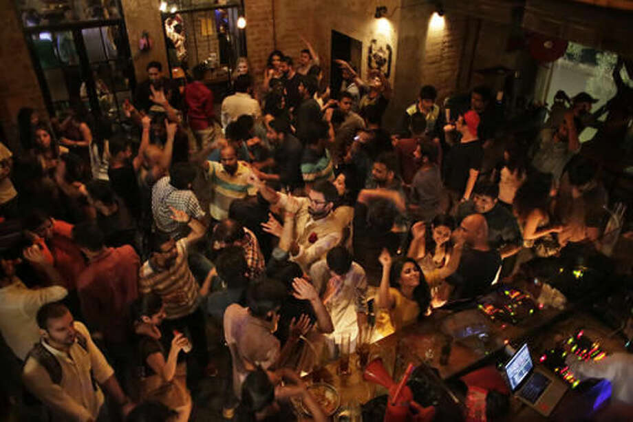 In this Sept. 10, 2016 photo, people dance at Social, a three-story destination on the edge of Hauz Khas Village, one of the most popular nightlife neighborhoods in New Delhi, India. However, after a night of thrills and spills, this watering-hole will be cleaned, rearranged, and transformed, into a cozy office where no one gets fired for drinking at work. As India emerges as one of the biggest markets in the world for tech-based startups, workspaces are transforming from traditional and hierarchal, to relaxed and bar-like. (AP Photo/Altaf Qadri)