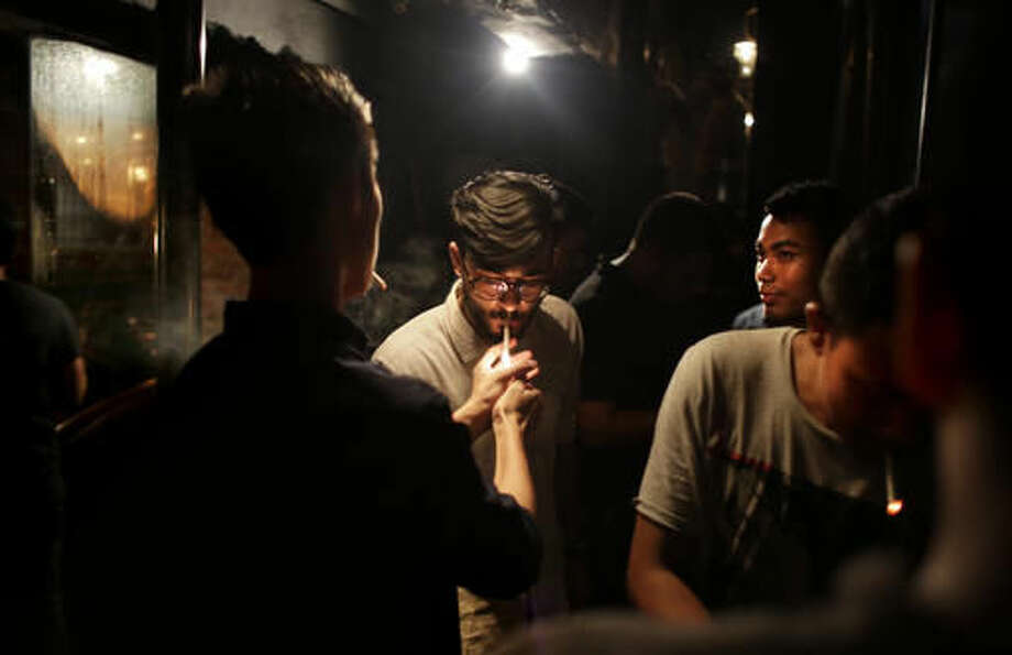 In this Sept. 10, 2016 photo, diners stand on the terrace for a smoke at Social, a three-story destination on the edge of Hauz Khas Village, one of the most popular nightlife neighborhoods in New Delhi, India. However, after a night of thrills and spills, this watering-hole will be cleaned, rearranged, and transformed, into a cozy office where no one gets fired for drinking at work. As India emerges as one of the biggest markets in the world for tech-based startups, workspaces are transforming from traditional and hierarchal, to relaxed and bar-like. (AP Photo/Altaf Qadri)
