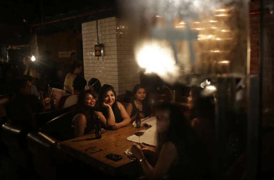 In this Sept. 10, 2016 photo, Indian women sit for a meal at Social, a three-story destination on the edge of Hauz Khas Village, one of the most popular nightlife neighborhoods in New Delhi, India. However, after a night of thrills and spills, this watering-hole will be cleaned, rearranged, and transformed, into a cozy office where no one gets fired for drinking at work. As India emerges as one of the biggest markets in the world for tech-based startups, workspaces are transforming from traditional and hierarchal, to relaxed and bar-like. (AP Photo/Altaf Qadri)