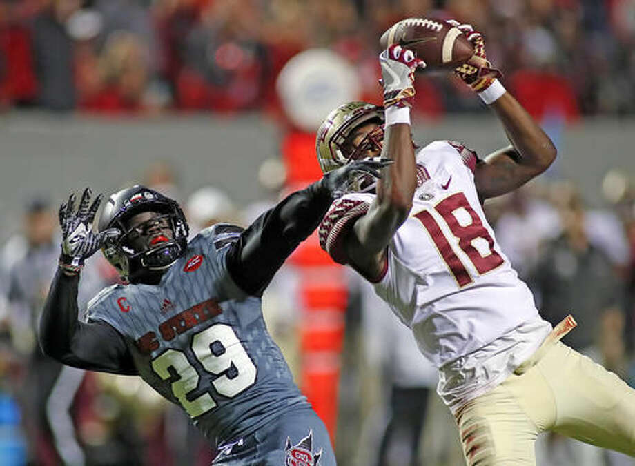Florida State wide receiver Auden Tate (18) hauls in a pass as he is defended by North Carolina State's Jack Tocho (29) during the first half of an NCAA college football game in Raleigh, N.C., Saturday, Nov. 5, 2016. (AP Photo/Karl B DeBlaker)