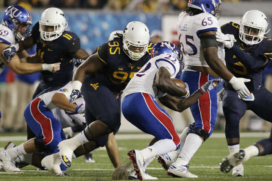 West Virginia defensive lineman Christian Brown (95) tackles Kansas running back Ke'aun Kinner (22) during the first half of an NCAA college football game, Saturday, Nov. 5, 2016, in Morgantown, W.Va. (AP Photo/Raymond Thompson)